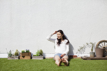 gradually: Woman sitting on the lawn Stock Photo