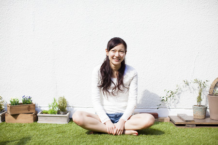 Woman sitting on the lawn Stock Photo