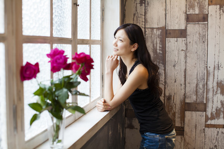 slowly: Woman standing at a window Stock Photo