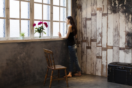 retrospective: Woman standing at a window Stock Photo