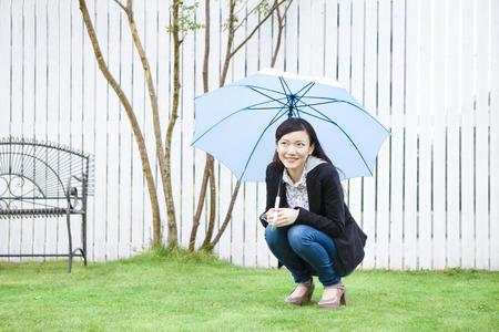 傘で座る女性