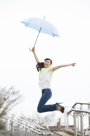 living moment: Woman to jump to have an umbrella