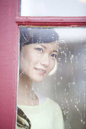 rain wet: Woman looking out through the window