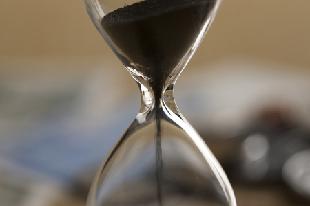 An hourglass and money