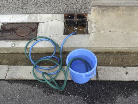 water hose: Water hose and bucket Stock Photo
