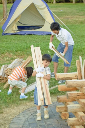 beings: Carry the wood for the campfire family Stock Photo