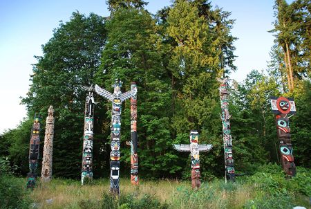 northwest indian art: Indian painted totem poles in Stanley Park, Vancouver Canada Stock Photo