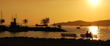 Silhouette of a couple enjoy beautiful sunset view in English Bay, Vancouver Canada photo