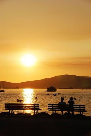 amazing stunning: Silhouette of a couple enjoy beautiful sunset view in English Bay Stock Photo