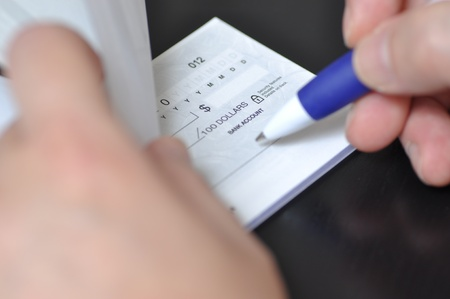 checkbook: Hombre sostener un bol�grafo para escribir cheque Foto de archivo