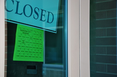 shop sign: Closed sign and business hours on window
