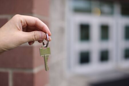 Business man handing key in front of building photo
