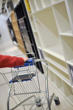 walk in closet: Woman pushing shopping cart in furniture store  Stock Photo