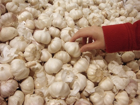 Woman buying garlic in supermarket photo
