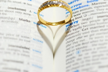 Wedding ring casting a heart onto a marry word photo