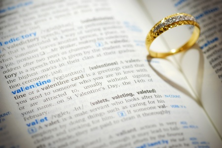 Wedding ring casting a heart onto a valentine word photo