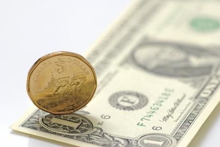 US one dollar bill vs Canadian one dollar coin  版權商用圖片