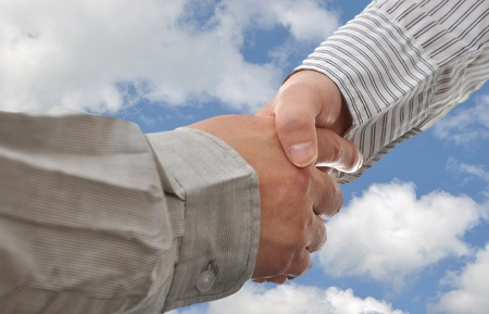 Hand shake between a businessman and a businesswoman with sky background
