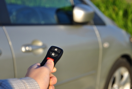 A hand holding car keys and a remote control for keyless entry   photo