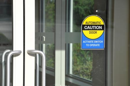 inform information: Automatic caution door sign Stock Photo