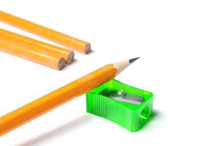 白い背景の上の sharpenr の削りくずと鉛筆します。