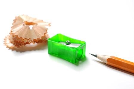 Pencil with sharpener shavings on white background