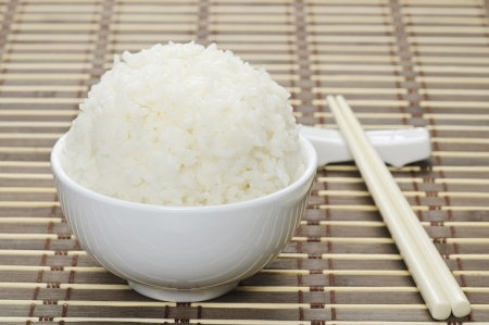 plato del buen comer: El arroz blanco cocido al vapor en un recipiente de cerámica y palillos