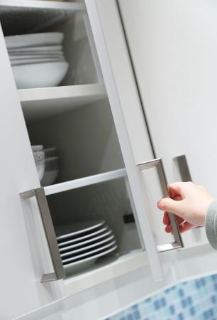 armoire cuisine: Femme d'ouverture ou de fermeture porte d'armoire de cuisine Banque d'images