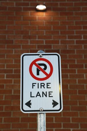 forewarning: No parking fire lane sign in front of red brick wall