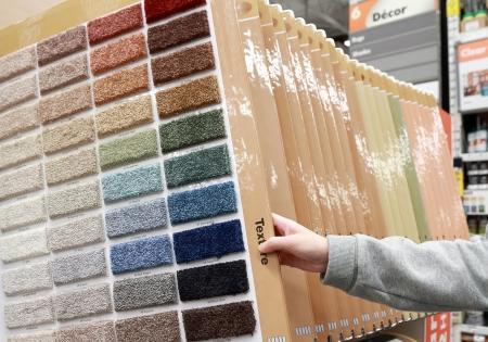 Woman choosing colorful carpet sample in store
