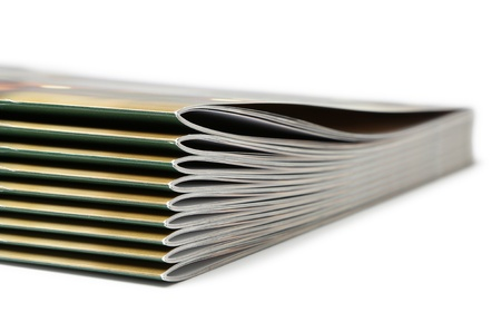 Stack of black covered magazines on white background photo