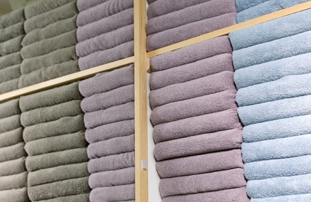 Piles of multicolored towels on the shelves in a shop Stock Photo