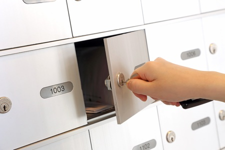 Woman holding key and opening mailbox Stock Photo