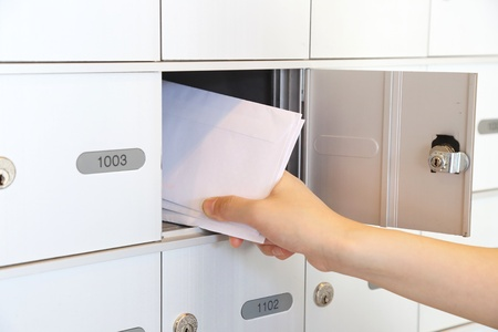 letterbox: Woman taking some letters from mailbox  Stock Photo