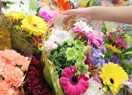 Woman hand picking a bouquet flowers in store  photo