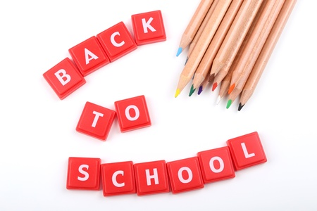 Back to school text and crayons over white background photo