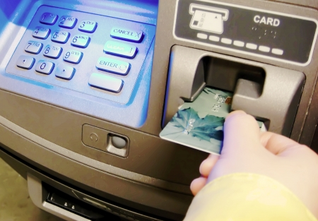 automatic teller machine: Woman insert card to withdraw money  Stock Photo
