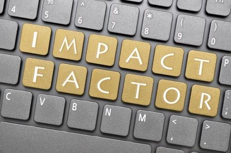 Brown impact factor key on keyboard Foto de archivo