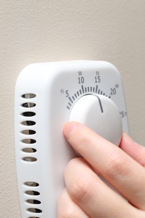 hands in the air: Woman hand setting a thermostat