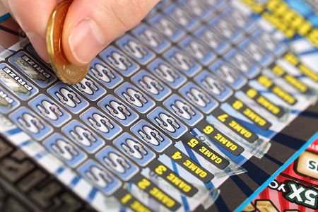A human hand is scratching a lottery ticket photo