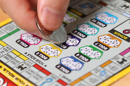 sanctioned: Coquitlam BC Canada - June 15, 2014 : Woman scratching lottery ticket called Monopoly. Its published by BC Lottery Corporation has provided government sanctioned lottery games in British Columbia since 1985.  Editorial
