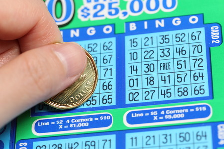 sanctioned: Coquitlam BC Canada - June 15, 2014 : Woman scratching lottery ticket called Bingo. Its published by BC Lottery Corporation has provided government sanctioned lottery games.