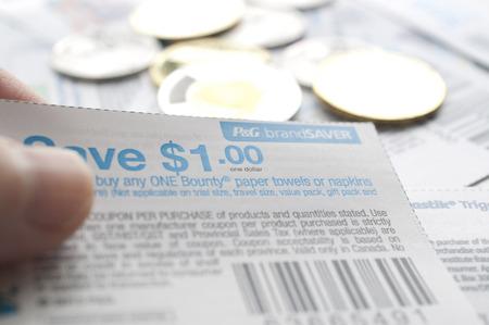 Coquitlam BC Canada - July 22, 2014 : Holding Canadian saving coupons with money. All coupons for Canadian store, they are issued by manufacturers of consumer packaged goods Canada.   Editorial