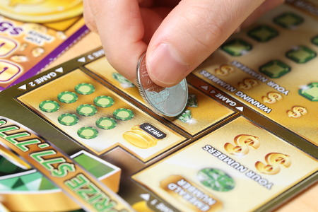 Coquitlam BC Canada - June 15, 2014 : Woman scratching lottery ticket called Monopoly. It's published by BC Lottery Corporation has provided government sanctioned lottery games.