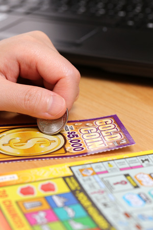 sanctioned: COQUITLAM, BC, CANADA - June 15, 2014 : Scratching lottery tickets. The British Columbia Lottery Corporation has provided government sanctioned lottery games in British Columbia since 1985.  Editorial