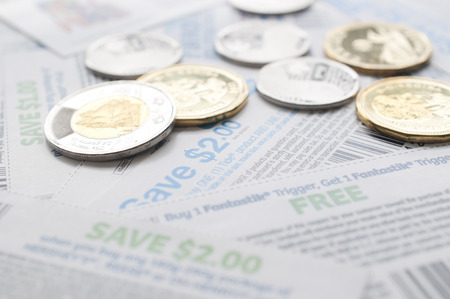 Coquitlam BC Canada - July 22, 2014 : Canadian saving coupons with money, focus on two dollar saving coupon. All coupons for Canadian store, they are issued by manufacturers of consumer packaged goods Canada. Editorial