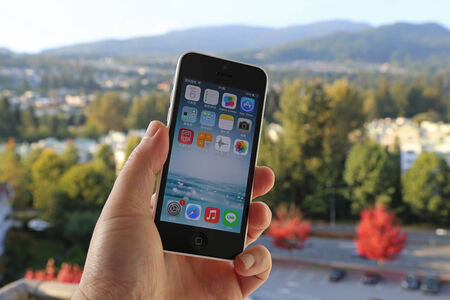 Coquitlam BC Canada - October 06, 2014 : Apple iPhone in a mans hand, the iPhone is one of the most popular smart phones in the world and produced by Apple Computer, Inc.