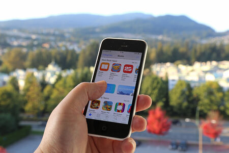 Coquitlam BC Canada - October 06, 2014 : Searching new app on iPhone with nature background, IPhone is one of the most popular smart phones in the world and produced by Apple Computer, Inc.