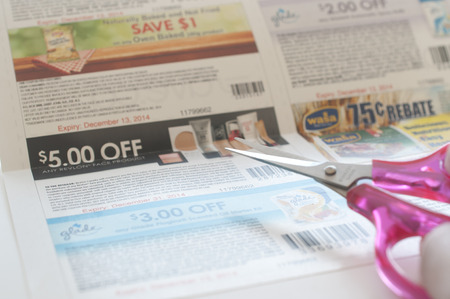 Coquitlam, BC Canada - November 11, 2014 : Woman prepare to cut coupon. All coupons for Canadian store, they are issued by manufacturers of consumer packaged goods Canada. Editorial