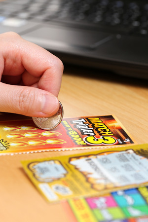 sanctioned: Coquitlam BC Canada - June 15, 2014 : Woman scratching lottery tickets. The British Columbia Lottery Corporation has provided government sanctioned lottery games in British Columbia since 1985.